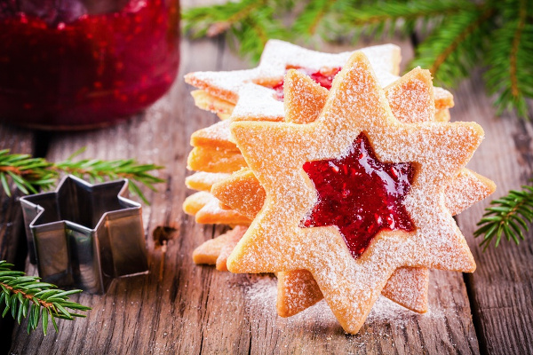 Christmas Linzer cookies with raspberry jam on a rustic wooden background